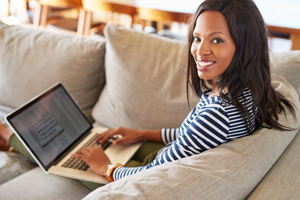young woman using a laptop while relaxing on a sofa at home