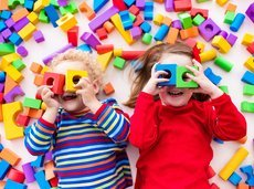 two happy preschool age children play with colorful plastic toy blocks