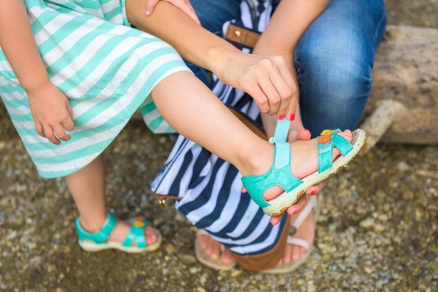 Mother helping her daughter to put on sandals