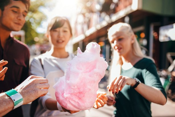 young people sharing cotton candy at amusement park