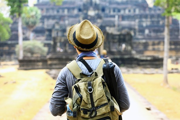 young traveler wearing a hat with backpack in Angkor Wat, Siem Reap, Cambodia