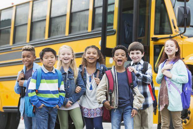 smiling school children in front of bus