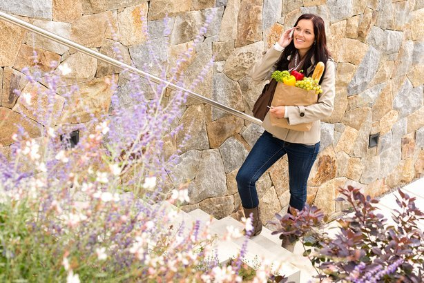 smiling woman climbing stairs talking phone shopping bag groceries