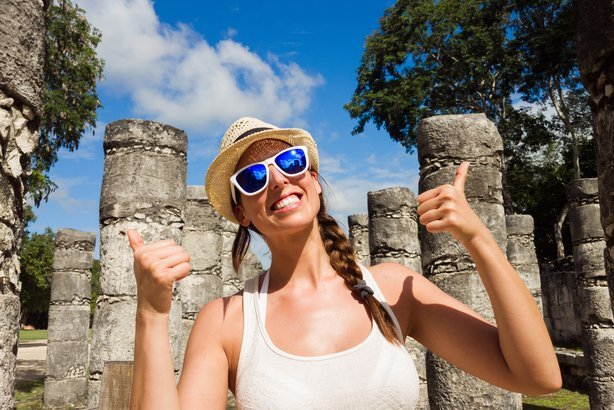 woman with her thumbs up, having fun at Chichen Itza ruins