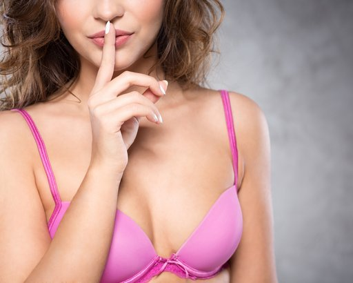woman wearing pink bra holding finger on her mouth