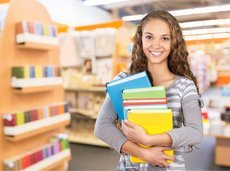 college student holding college textbooks in college bookstore