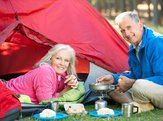 Senior couple cooking breakfast on a camping trip