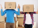 couple with boxes and mad faces pen marked on them, in the midst of packing