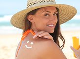woman applying suncream at the beach in the shape of smiley face