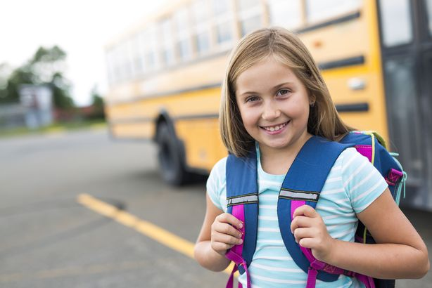 girl student with backpack in front of school bus