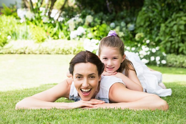 mother and daughter laying on grass in yard