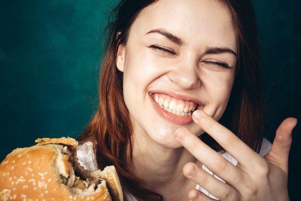 woman laughing and eating a hamburger