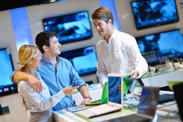 young couple in consumer electronics store looking at laptops with customer service help