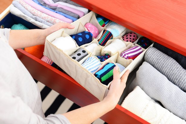konmari woman putting folded clothes into drawer