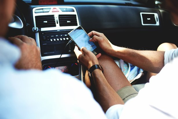 man using navigation on mobile phone while sitting on front passenger seat with driver