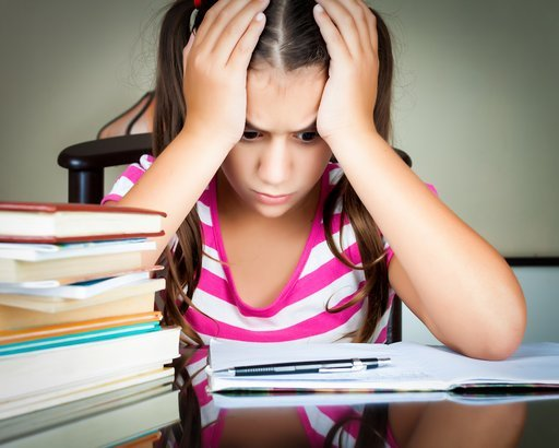 frustrated schoolgirl studying with a pile of books on her desk