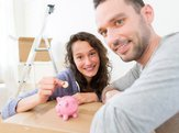 young couple saving money in a piggy bank