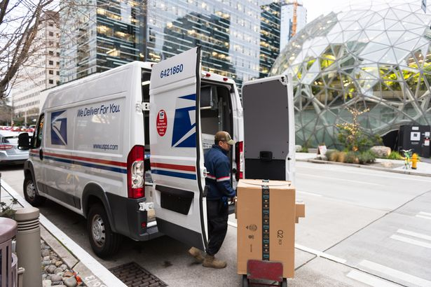 USPS truck as a driver delivers Amazon packages in Seattle