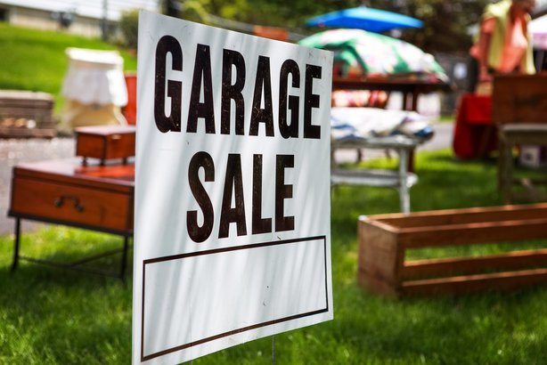 garage sale sign on the shady lawn of a suburban home