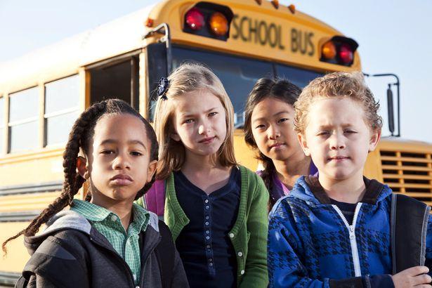 serious-looking children in front of schools