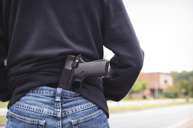 person's back with gun tucked into jeans facing school building