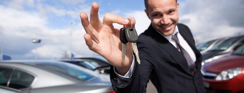 happy dealer holding car keys outdoors
