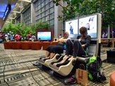 people at the airport in massage chairs