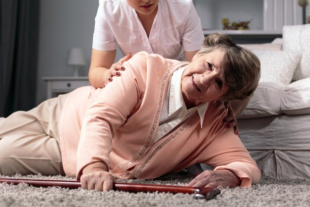 disabled older woman fallen on floor and caring young assistant