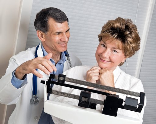 doctor with satisfied woman on medical scale in doctor's office