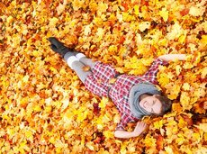 woman falling into autumn leaves