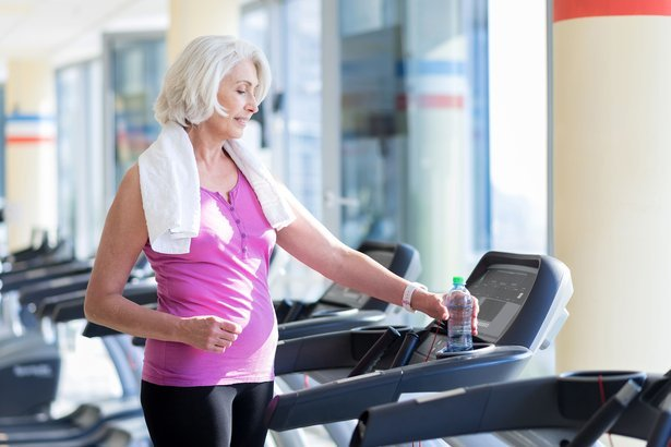 relaxed smiling gray haired woman standing on treadmill