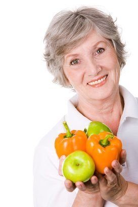 senior female holding apples and peppers in hands