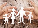 family cutout protected by hands on wooden table