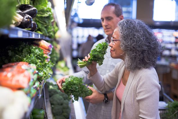 senior couple selecting fresh herbs at the grocery store