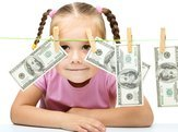 child hiding behind money on laundry line