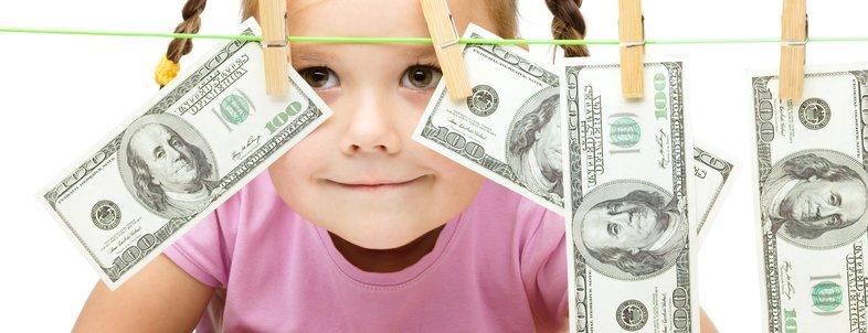 child hiding behind money on laundry line
