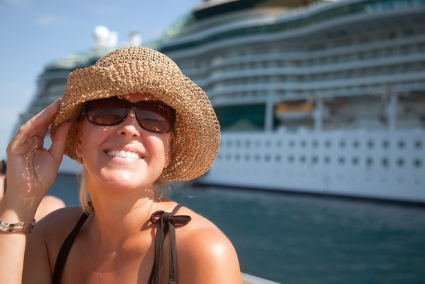 happy woman on tender boat with cruise ship in the background