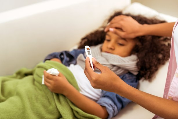 little African American girl with scarf on her neck is ill, lying in bed with temperature