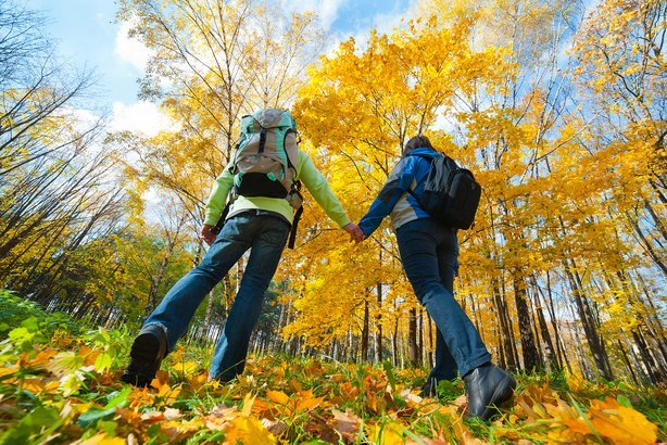 young couple with backpacks in the park during fall
