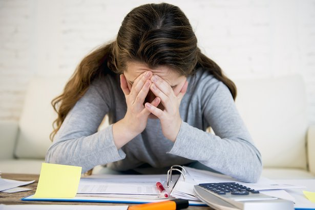 Young stressed out woman paying bills