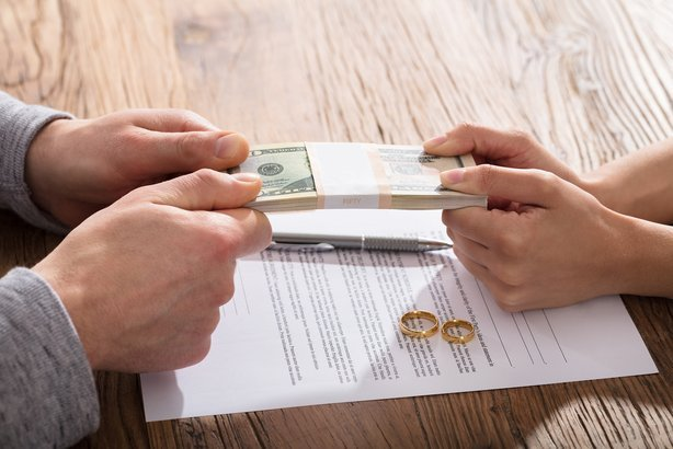 couple fighting for money over the divorce agreement with gold wedding rings