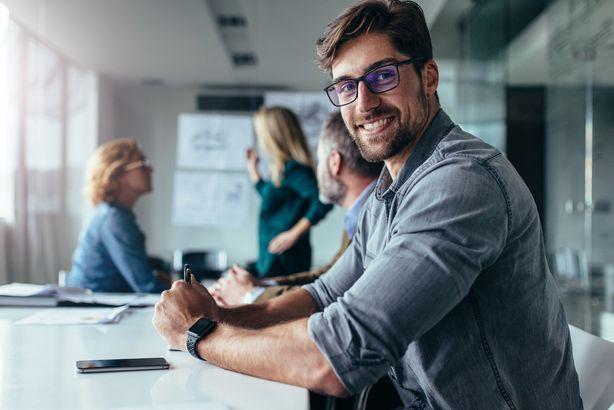 happy businessman sitting in board room during presentation