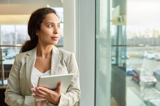 mixed-race businesswoman looking out window