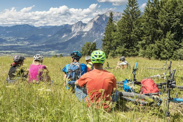 group of people wearing bike helmets while sitting in the grass with their bikes, mountains in background