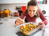 woman in kitchen putting rosemary on squash dish