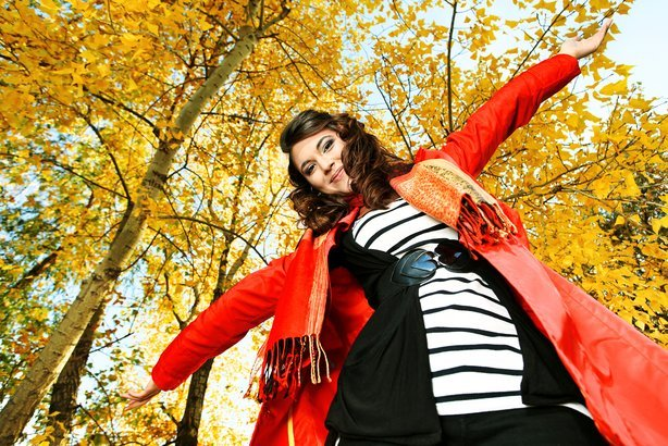 Happy fashionable woman in a park during autumn