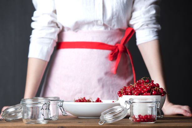woman's torso standing over table with bowl, mason jars, and lingonberries