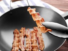 holding tasty bacon slice with tongs over pan