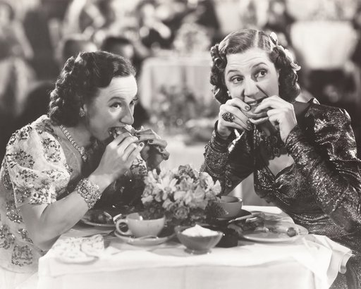 two women distracted from their meal during the 1940s