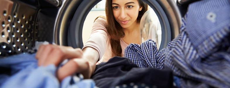 woman doing laundry reaching inside washing machine